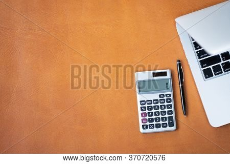 Flat Lay, Top View Office Table Desk. Workspace With Calculator,pen,laptop On Brown Leather Backgrou