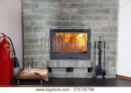 Front View Of A Gray Brick Fireplace With A Blazing Fire Behind A Glass Door. A Red Fire Extinguishe