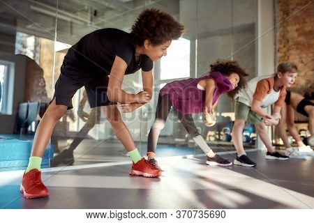 Portrait Of A Boy Smiling While Warming Up, Exercising Together With Other Kids In Gym. Sport, Healt