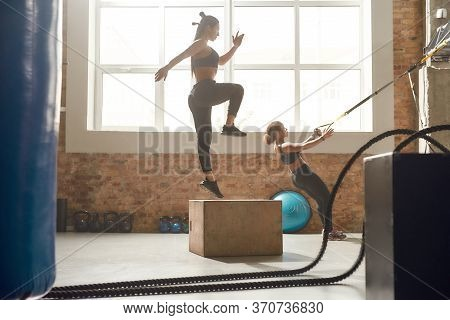 Full-length Shot Of Sportive Women Having Workout At Industrial Gym. Jumping Using Plyo Box And Doin