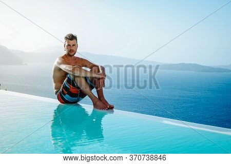 Santorini Greece Oia, Young Men In Swim Short Relaxing In The Pool Looking Out Over The Caldera Of S
