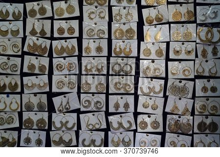 Indian Earrings Kept In Small Plastic Pouches For Sale In The Local Market. Variety Of Earrings Made