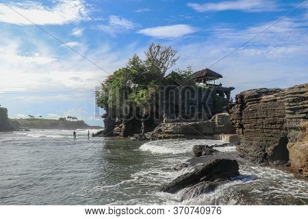 Sacred Balinese Temple In Tanah Lot. Pura Batu Bolong On Coastline With Hole In Rock. Traditional St