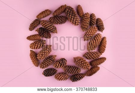 Christmas Wreath Of Fir Cones On A Pink Background Copy Space. Winter Decor Made Of Cones. Round Fra