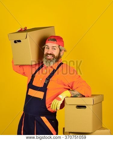Bearded Man Courier Hold Boxes. Moving To New Apartment. Post Service. Bearded Loader In Uniform. Re