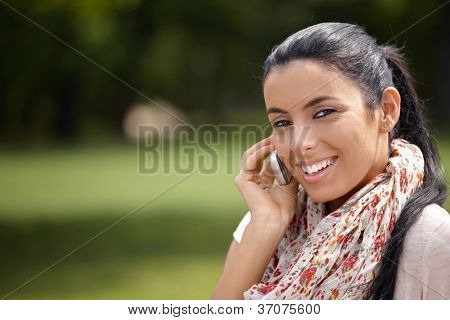 Pretty girl talking on mobile phone in park, smiling at camera.