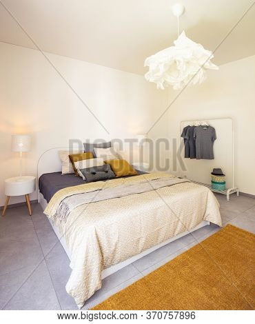Interior of elegant double bedroom. Colorful blankets and pillows and a clothes drying rack in the background