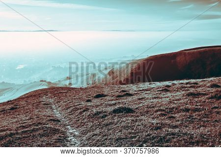 Mystical Mountain Landscape With Gray Dry Ground, Surreal View Of Morning Fog Filling Valleys Of Hil