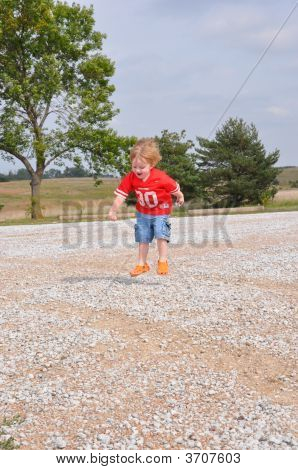 Child Jumping On Gravel