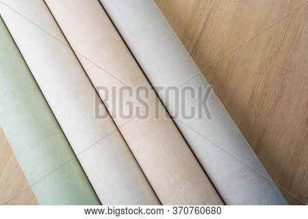 Rolls Of Multi-colored Paper Wallpaper On A Wooden Table
