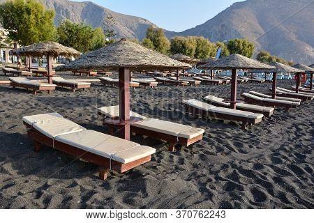 Tanning Beds And Umbrellas On Perissa Beach, Santorini, Greece.