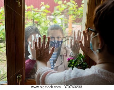 Two Granddaughters Standing Behind The Window In Protective Masks And Holding Their Hands On The Gla