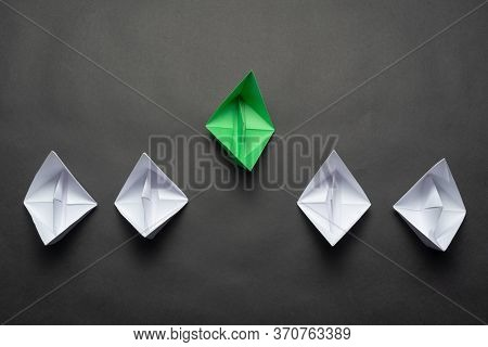 Flat Lay Green Origami Origami Leader Boat Ahead Others Boats. Row Of Paper Ships On Black Backgroun