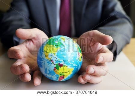 Globe Side With America, Hands Try To Support The Planet From Threats. Symbol Of The Unification Of