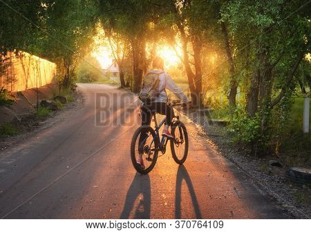 Woman Riding A Bicycle On The Rural Road At Sunset In Summer. Colorful Landscape With Sporty Girl Wi