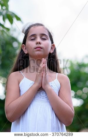 Girl In A White Dress, Praying In The Morning. Prayer With The Hands Stuck Together, With An Unfocus