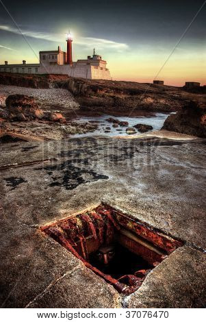 Face of a person hidden underground peeking out in the sewer gutter near a lighthouse in the evening