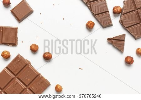 Bar And Pieces Of Milk Chocolate, Hazelnut On White Background Flat Lay Top View Copy Space. Minimal