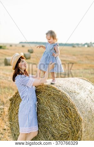 Happy Mother And Little Daughter, Wearing Similar Striped Dresses, Having Fun In Summer Field With G