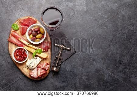 Cheese, meat and olives antipasto. Appetizer selection on wooden board and glass with red wine. Top view with copy space. Flat lay