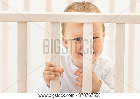 Portrait Of A Baby In A Crib, A 2-year-old Baby In A Crib
