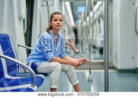 Positive Brunette Girl Using Cell Phone At Subway