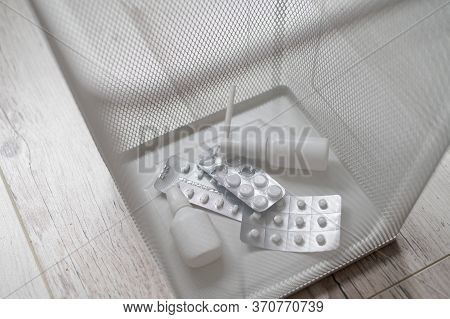Medication In A White Mesh Metal Wastebasket. Pills Thrown Into The Trash. A Paper Basket With Medic