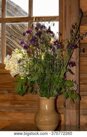 A Bouquet Of Garden Flowers Against A Wooden Wall In A Clay Pot Closeup