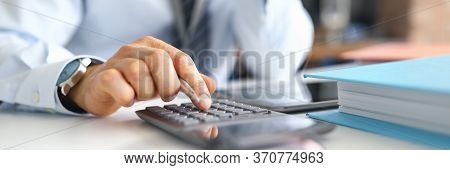 Hand Of Male Businessperson Making Investment And Income Data Calculations At Office Worktable Close
