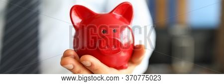 Male Businessman Hold In Hand Red Little Piggybank As Symbol Of Financial Success And Reasonable Mon
