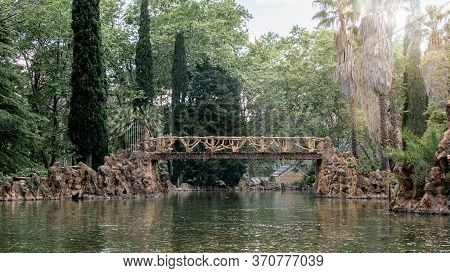 Wooden Openwork Bridge Over The Lake In Natural Park. Detail Of Spanish Ancient Architecture.