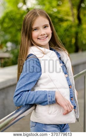 Adorable Smiling Little Girl Child Preteen Standing In The Park Outdoors. Fashion Concept