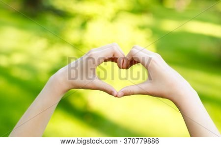 Child Hands On Heart-shaped Bokeh Background Blurred Outdoor. Handmade Heart With Female Hands