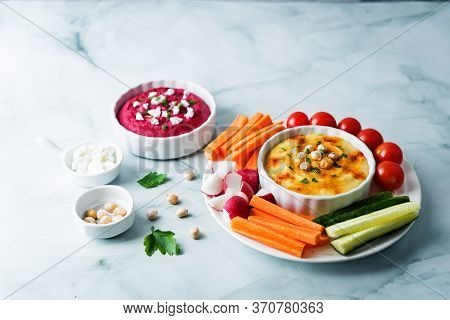 Set Of Classic Hummus And Beet Hummus Appetizers With Carrot, Radish, Tomato And Cucumber