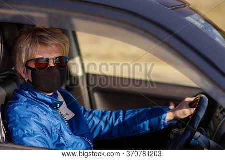 Woman in black face mask and sunglasses is driving a car and lookiing in the driver\'s opened window.She\'s hand is on the drive, right-hand drive. Coronavirus infection control concept.