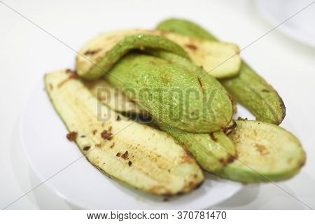 Close-up Of Baked Delicious Green Zucchini. Juicy Vegetable Served On White Plate With Pepper. Tasty
