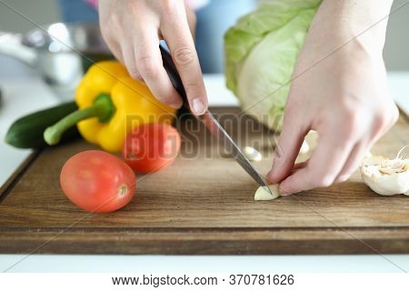 Close-up Of Womans Hand Cutting Garlic With Sharp Silver Knife On Wooden Board. Whole Yellow Pepper