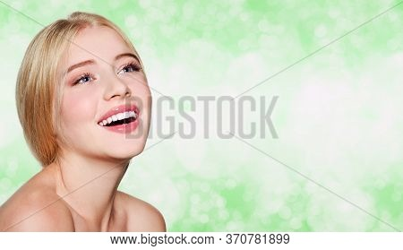 Beautiful Smiling Young Woman Girl Face With Great White Teeth And Clean Skin On A Blur Green Backgr