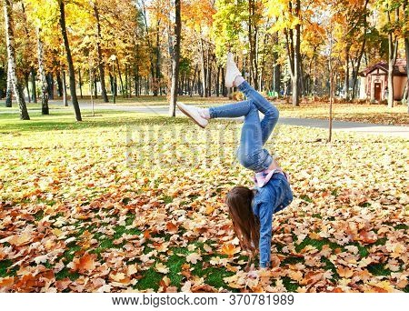 Autumn Portrait Of Adorable Smiling Gymnast  Little Girl Child Preteen Having Fun In The Park Outdoo