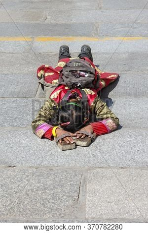 Little Girl Wearing Traditional Red Cloathes With Wooden Protection On Hands Praying In Prostration