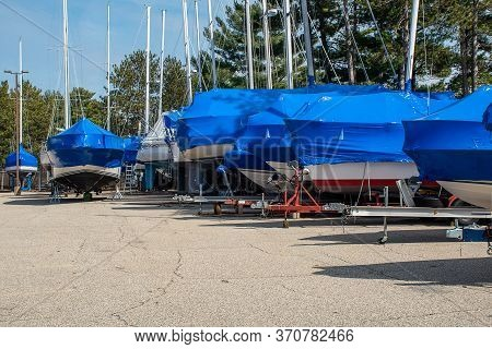 Row Of Sailboats With Blue Shrink Wrap Covers In Outdoor Storage Lot