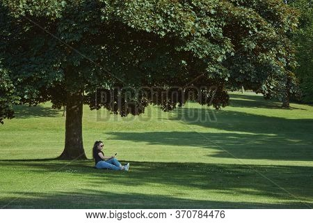 Portrait Of A Woman In A Sunglasses Sitting On Grass In The Park Near Big Tree, Sunny Summer Day. Wo