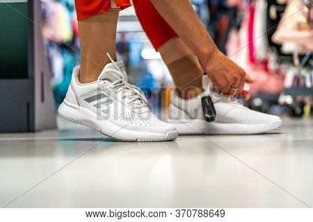 Olomouc June 9, 2020: Woman Chooses And Tries Sports Shoes Adidas In The Store