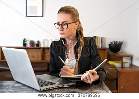 Young Woman With Eyeglasses, Headphones, Laptop Studying Working Online Writing Note Pad. Watching O
