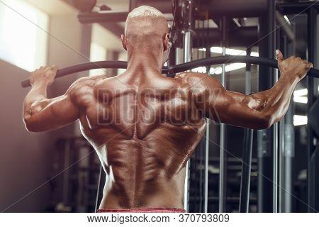 Muscular Bodybuilder Fitness Man Doing Pull-ups Exercises In Gym Naked Torso. Handsome Strong Athlet