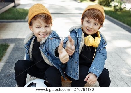 Two Happy Twin Boys Sitting On The Skateboard Or Pennyboard Showing Thumbs Up In The Street.