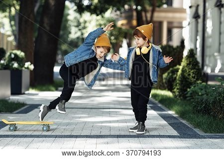 Two Funny Twin Boys Play With Skateboard Or Pennyboard With Happy Faces In The Street.
