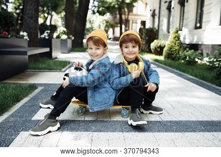 Two Joyful Twin Boys Sitting On The Skateboard Or Pennyboard Posing With Happy Faces In The Street.