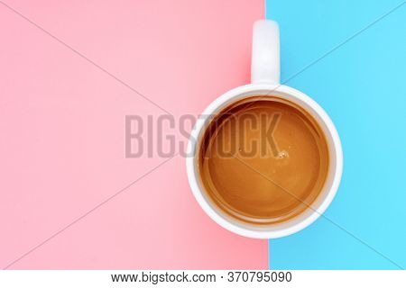 Cup of coffee on a gently pink and turquoise background. Top view flat lay
