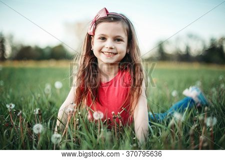 Cute Adorable Caucasian Girl Among Dandelions Flowers. Child Lying In Grass On Meadow. Outdoor Fun S